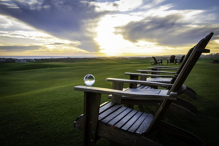 sitting on a chair watching the sunset and looking for used golf balls